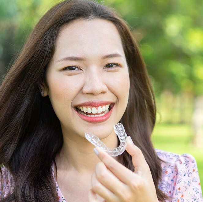 Woman placing Invisalign clear braces alignment tray