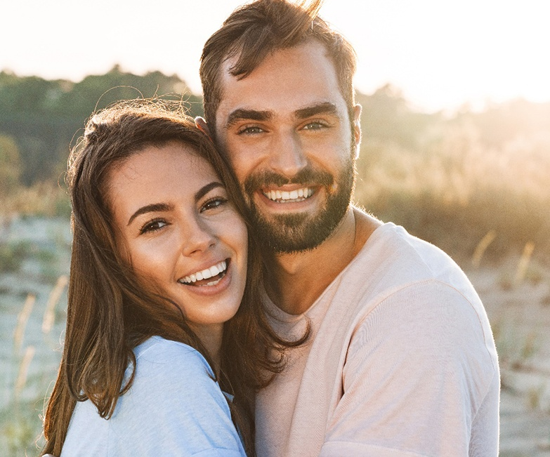 Couple hugging outside; smiling with dental crowns in Jacksonville, FL