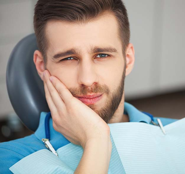 Man at emergency dentistry appointment holding cheek