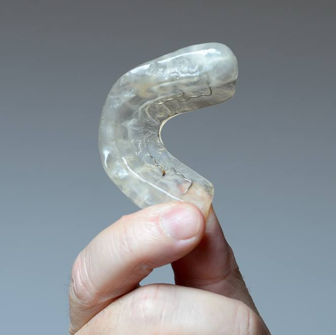 Hand holding an occlusal splint for TMJ therapy